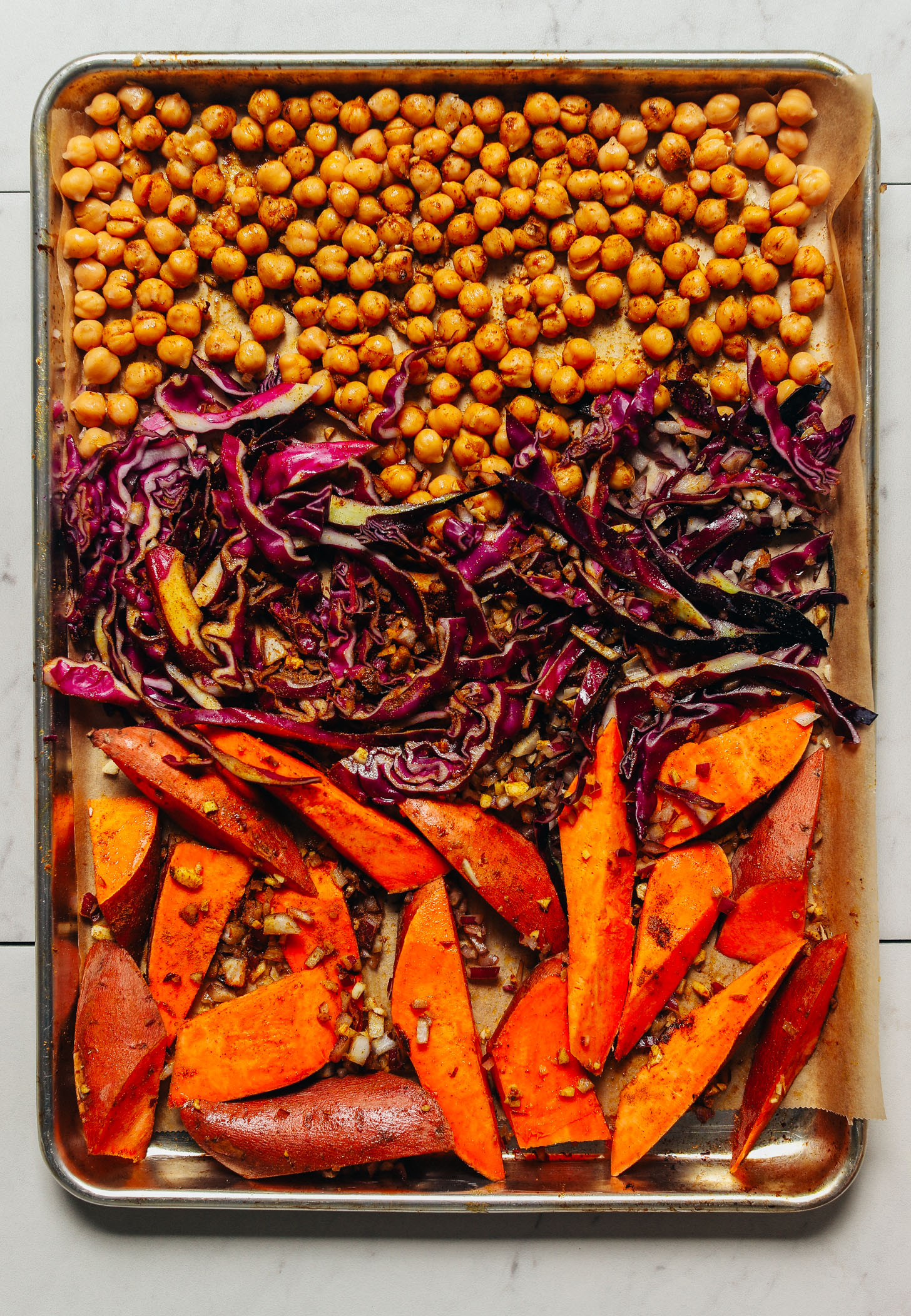 Baking sheet filled with sweet potatoes, cabbage, and chickpeas topped with curry powder