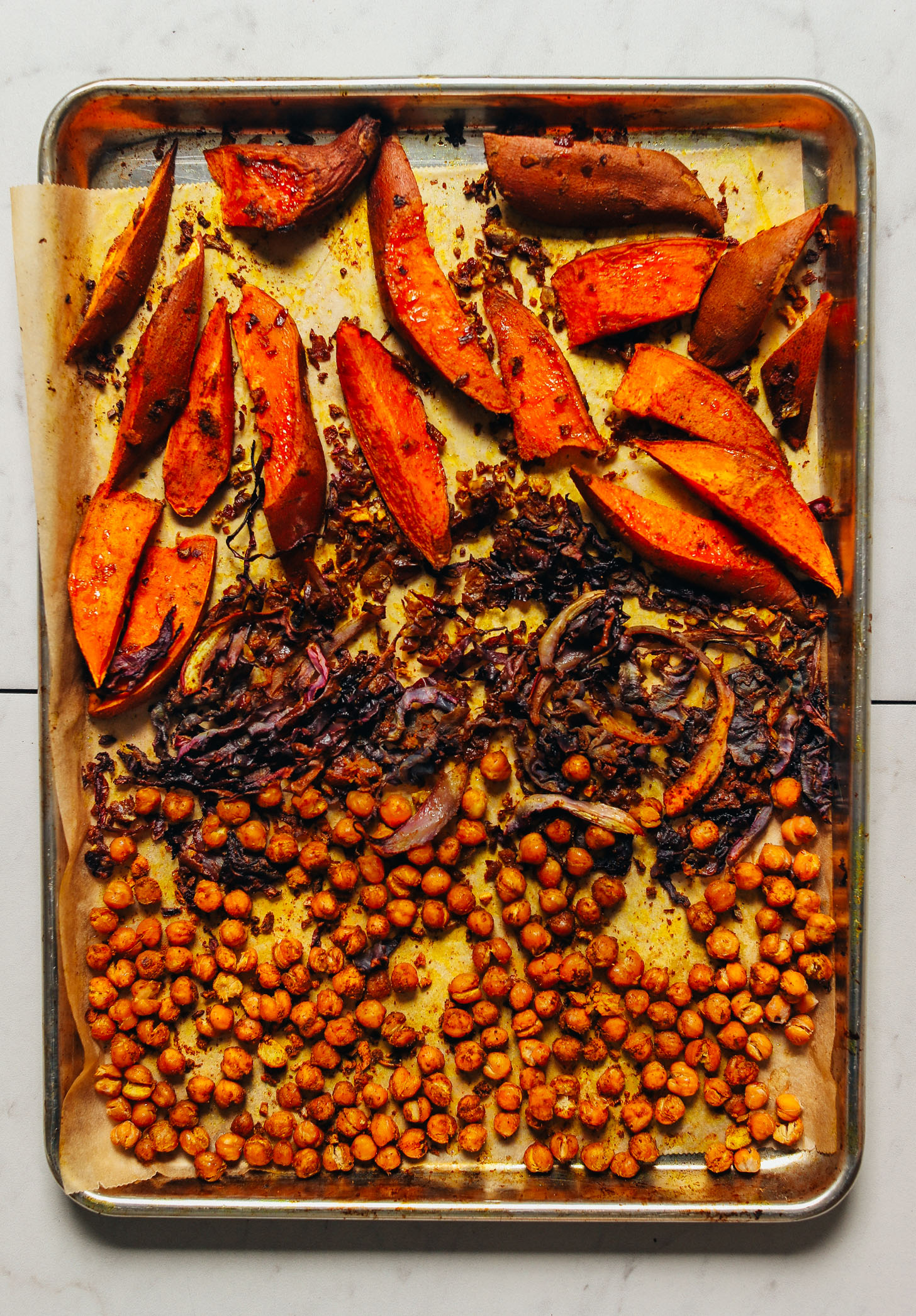 Baking sheet filled with freshly roasted cabbage, chickpeas, and sweet potatoes for a simple vegan Sheet Pan Dinner