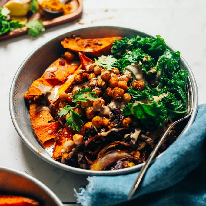 Bowl filled with a serving of our Sheet Pan Dinner recipe made with Curried Sweet Potatoes, Crispy Chickpeas, Cabbage, and Greens