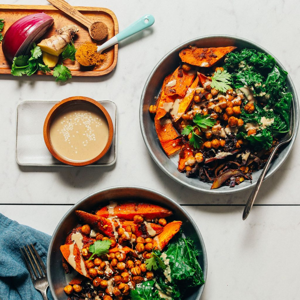 Bowls of our Sweet Potato Sheet Pan Dinner recipe beside a bowl of tahini sauce