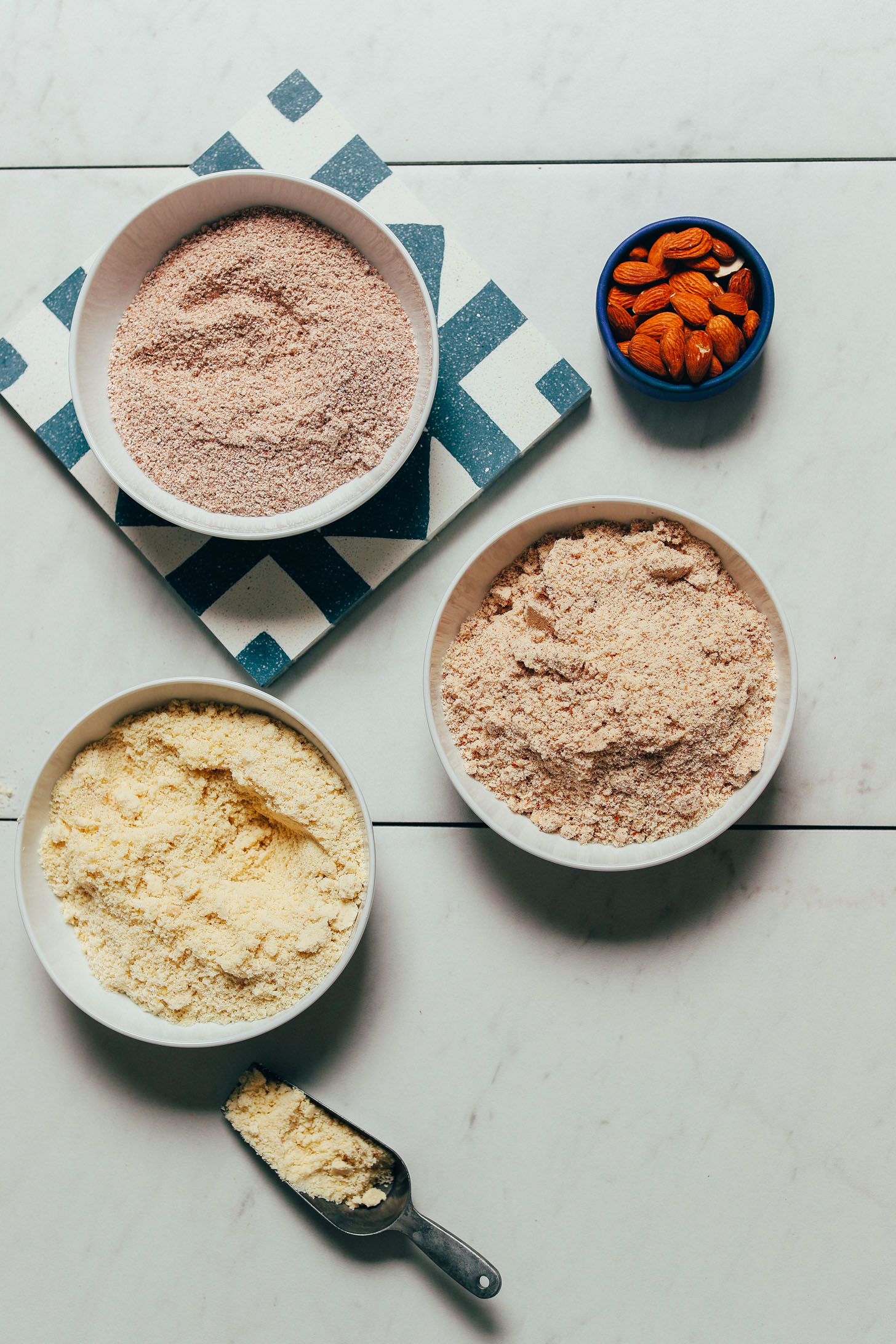 Bowls of almond flour and two different types of almond meal with one being made from leftover almond pulp