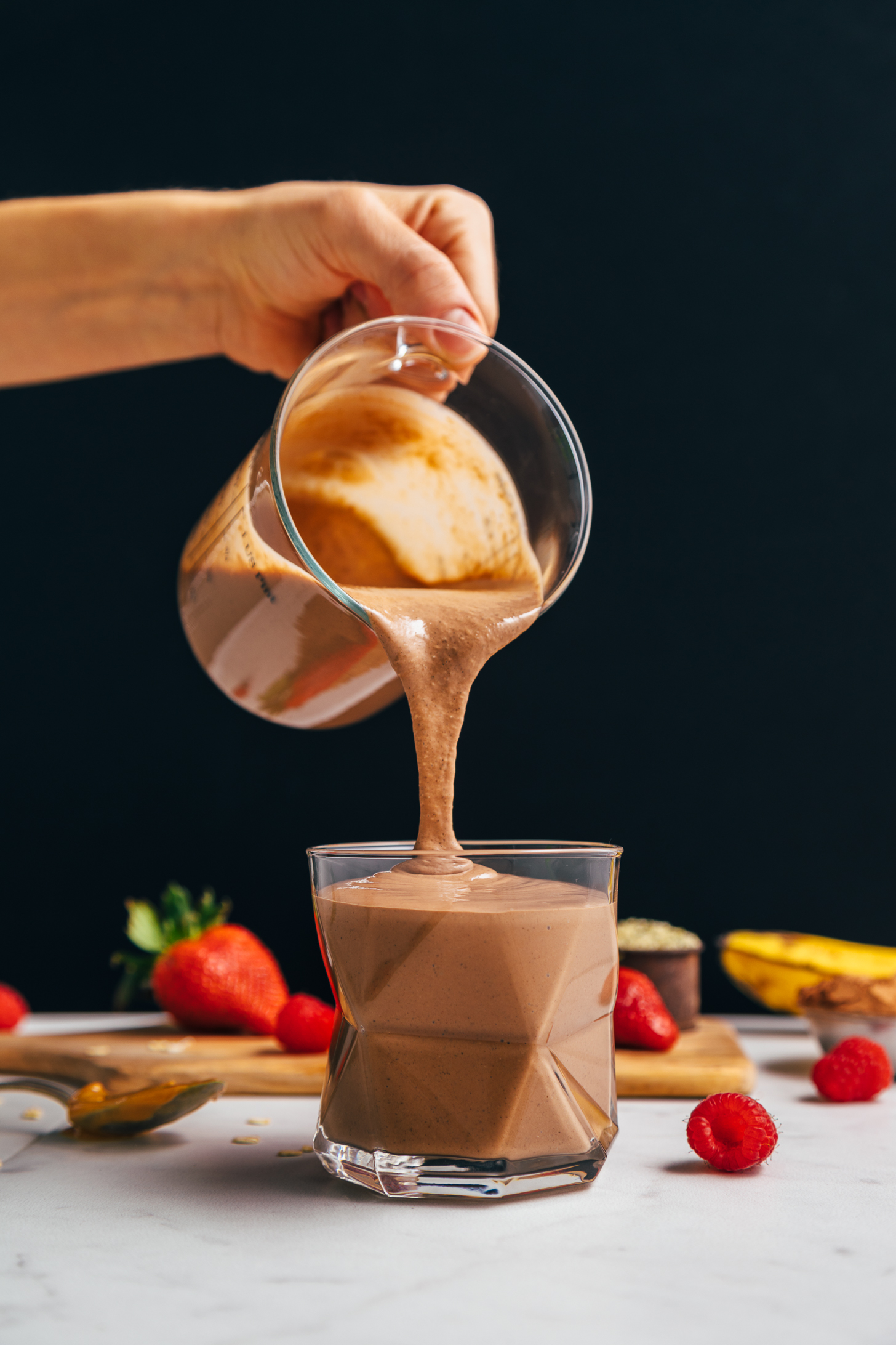 Pouring a serving of our Chocolate Protein Shake from a measuring glass
