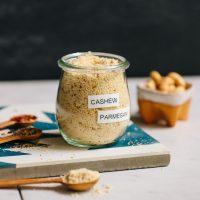 Jar of yeast-free Vegan Parmesan Cheese beside cashews and spices to make it