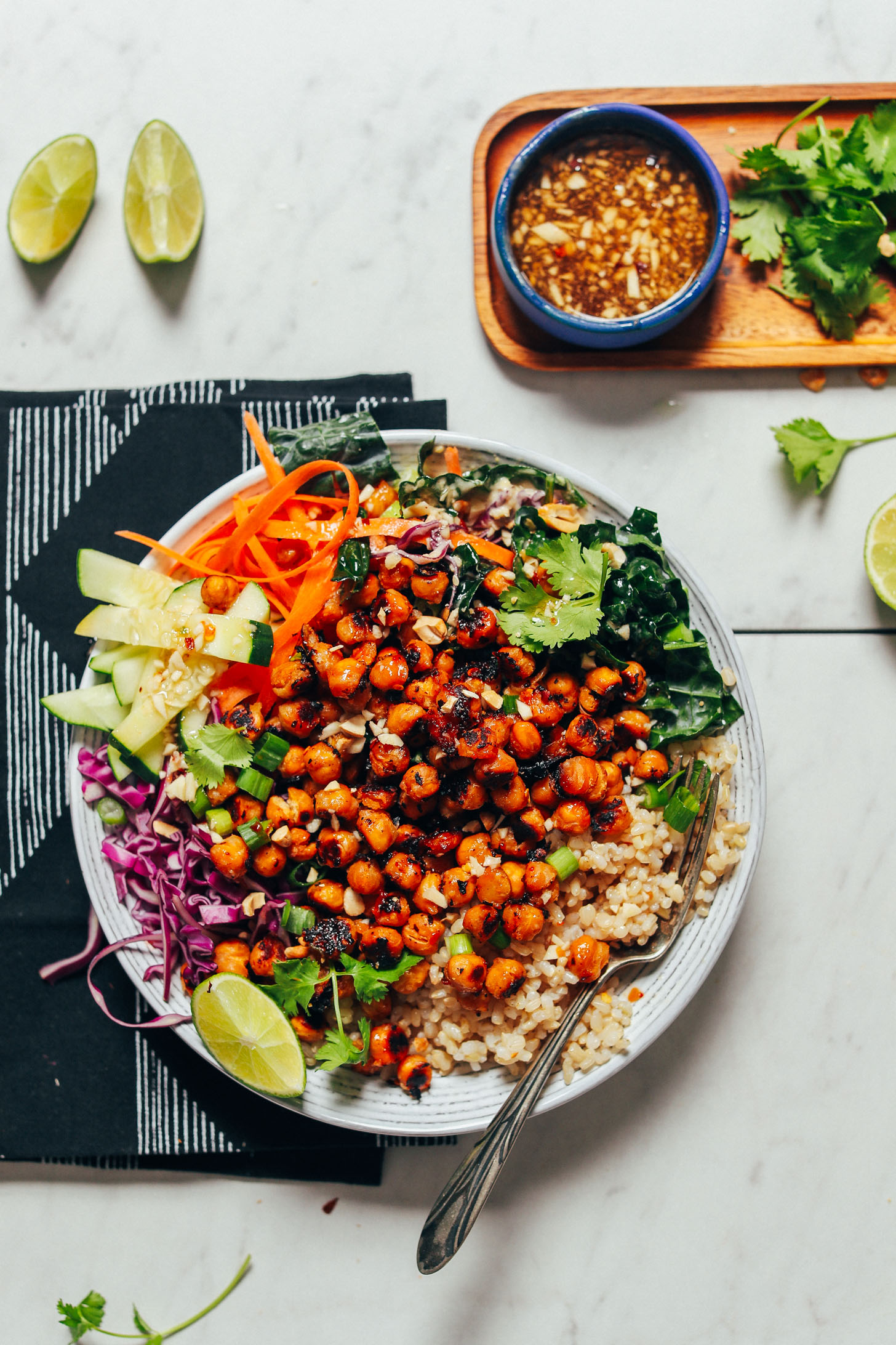 Bowl of brown rice, fresh vegetables, Miso Chickpeas, cilantro, and lime wedges surrounded by more ingredients for serving