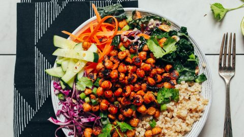 Crispy Miso Chickpea Bowl alongside fresh lime, chopped cashews, dressing, and cilantro for serving