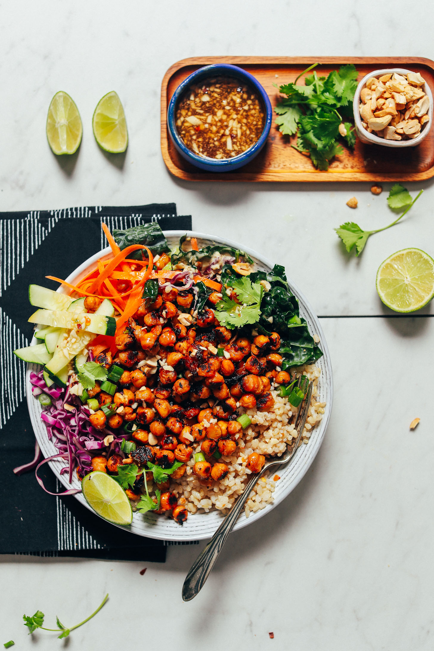 Crispy Miso Chickpea Bowl beside serving ingredients including cilantro, dressing, cashews, and lime
