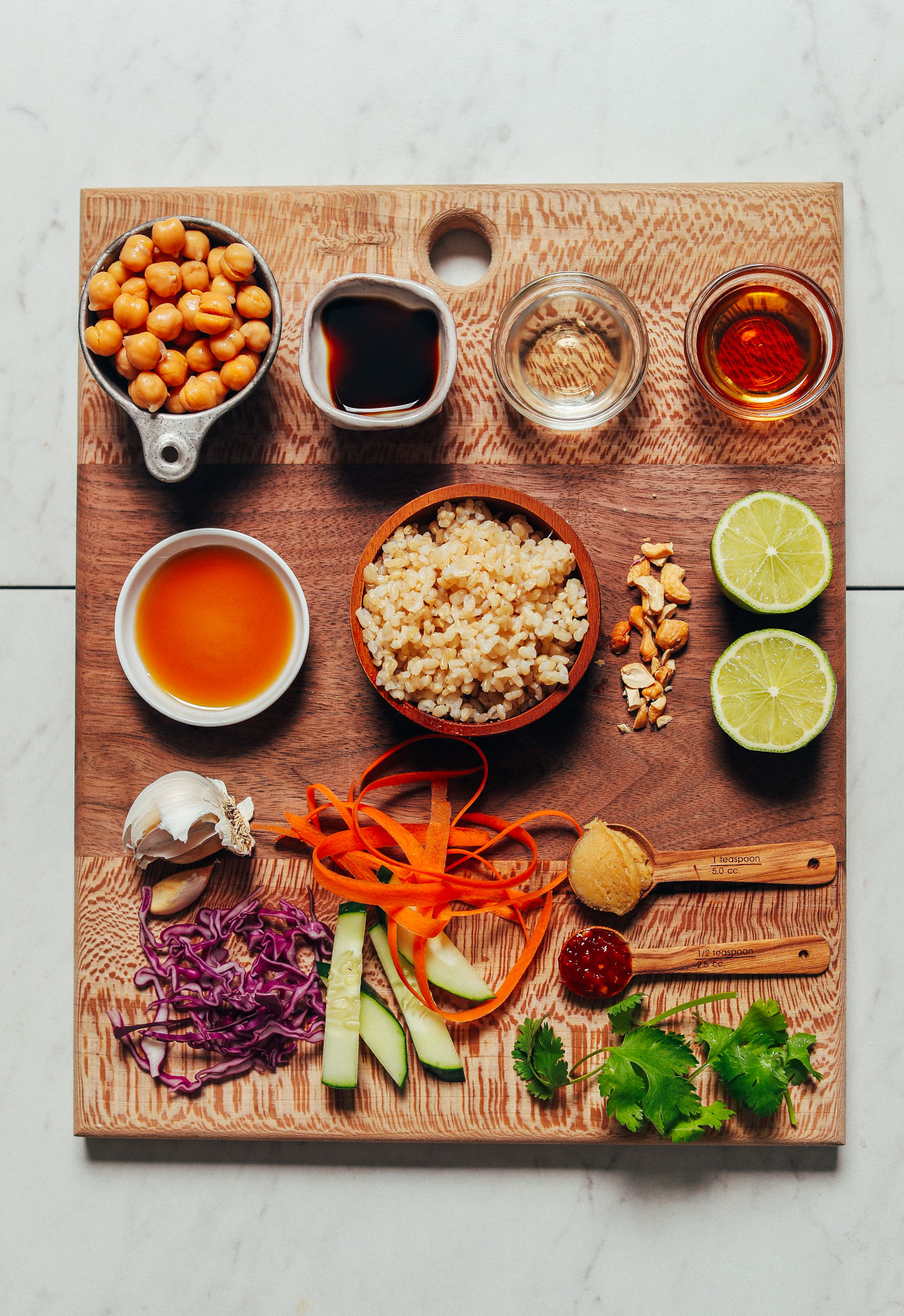 Wood cutting board with ingredients for making our Crispy Miso Chickpea Bowls with Garlic Sesame Dressing recipe