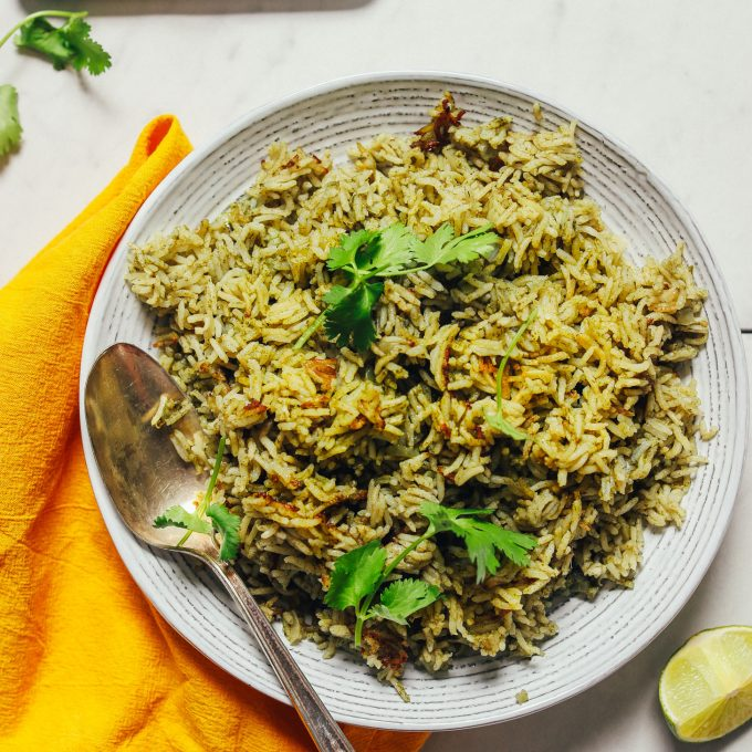 Bowl of homemade Green Rice beside a plate of jalapeno, lime, and cilantro used to make it