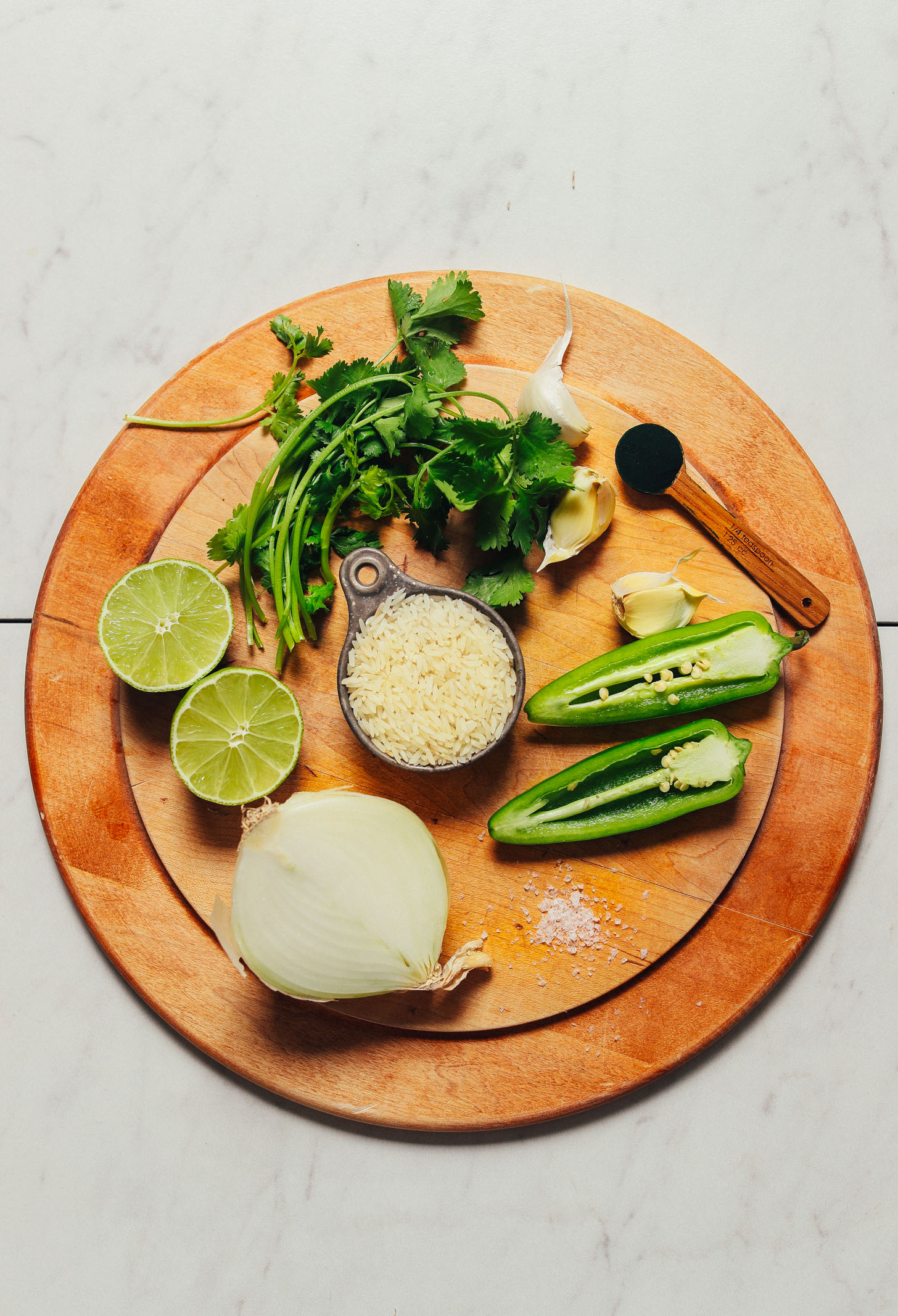Wood cutting board with ingredients for making our Mexican-inspired Green Rice recipe
