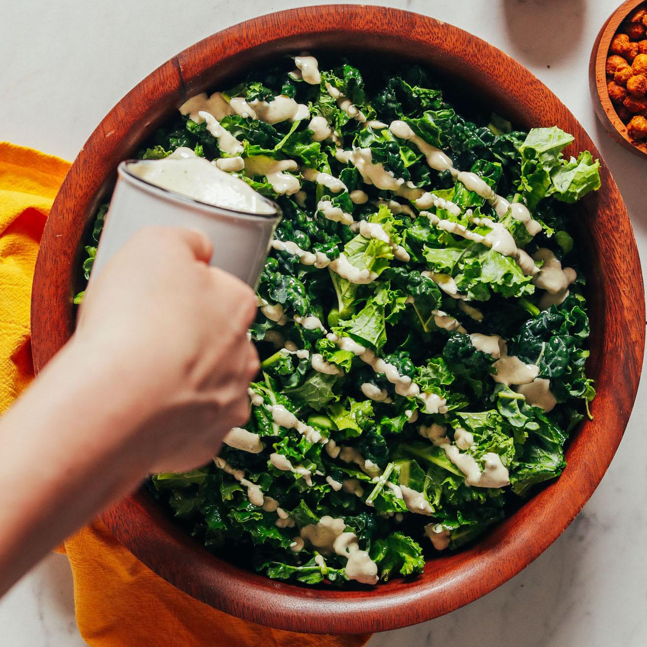Drizzling vegan Caesar Dressing onto a kale salad