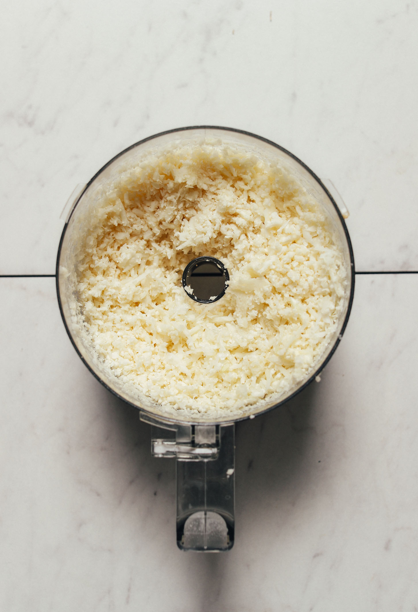 Food processor filled with freshly made homemade cauliflower rice