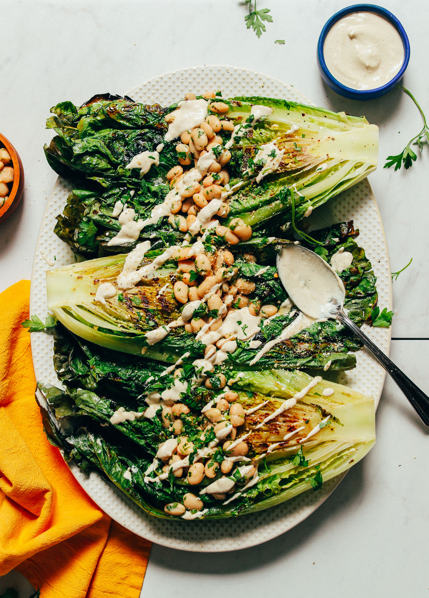 Platter of broiled romaine topped with Herbed Beans and drizzled with Vegan Caesar Dressing