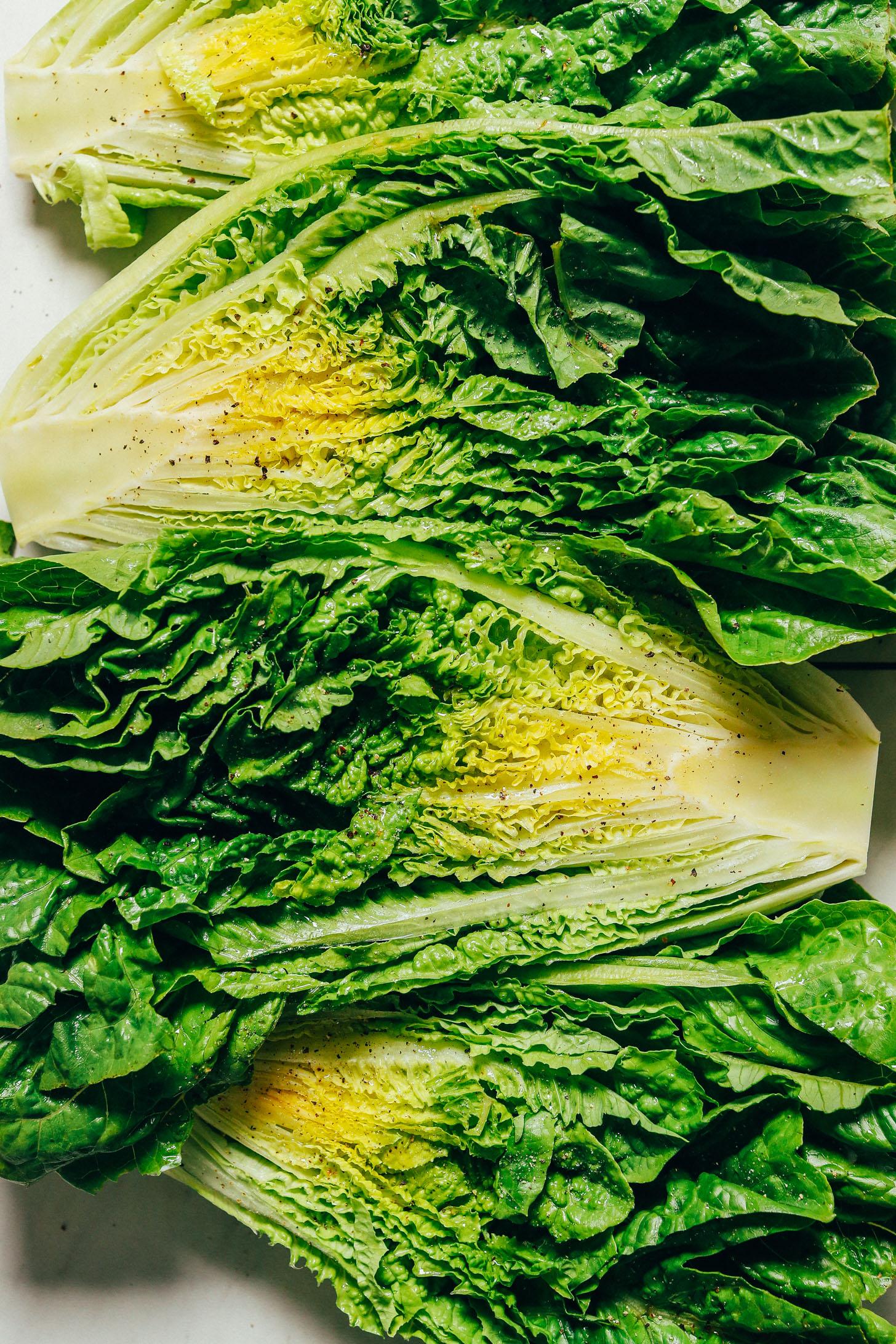 Halved heads of romaine lettuce sprinkled with black pepper