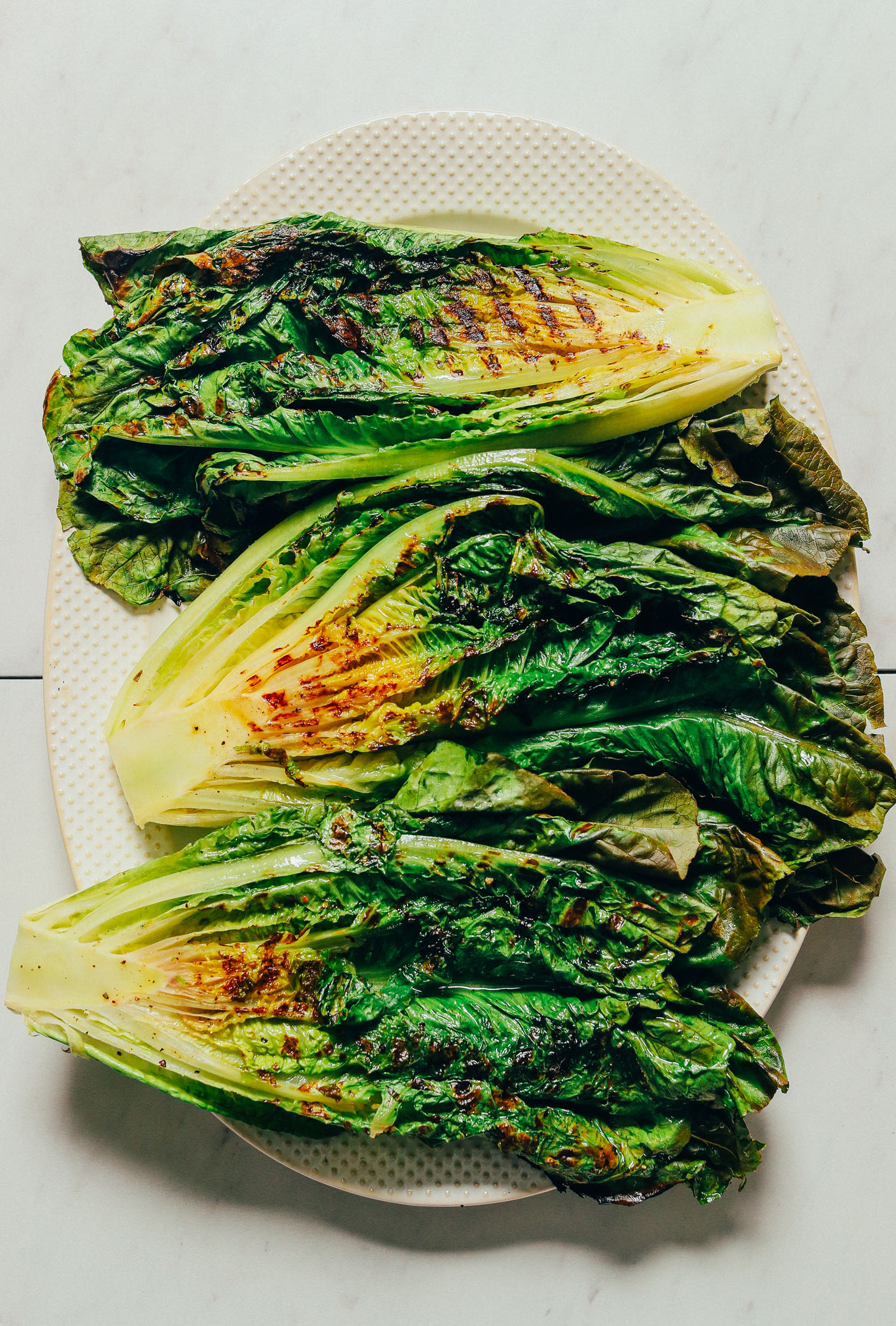 Platter of halved romaine heads grilled on a grill pan