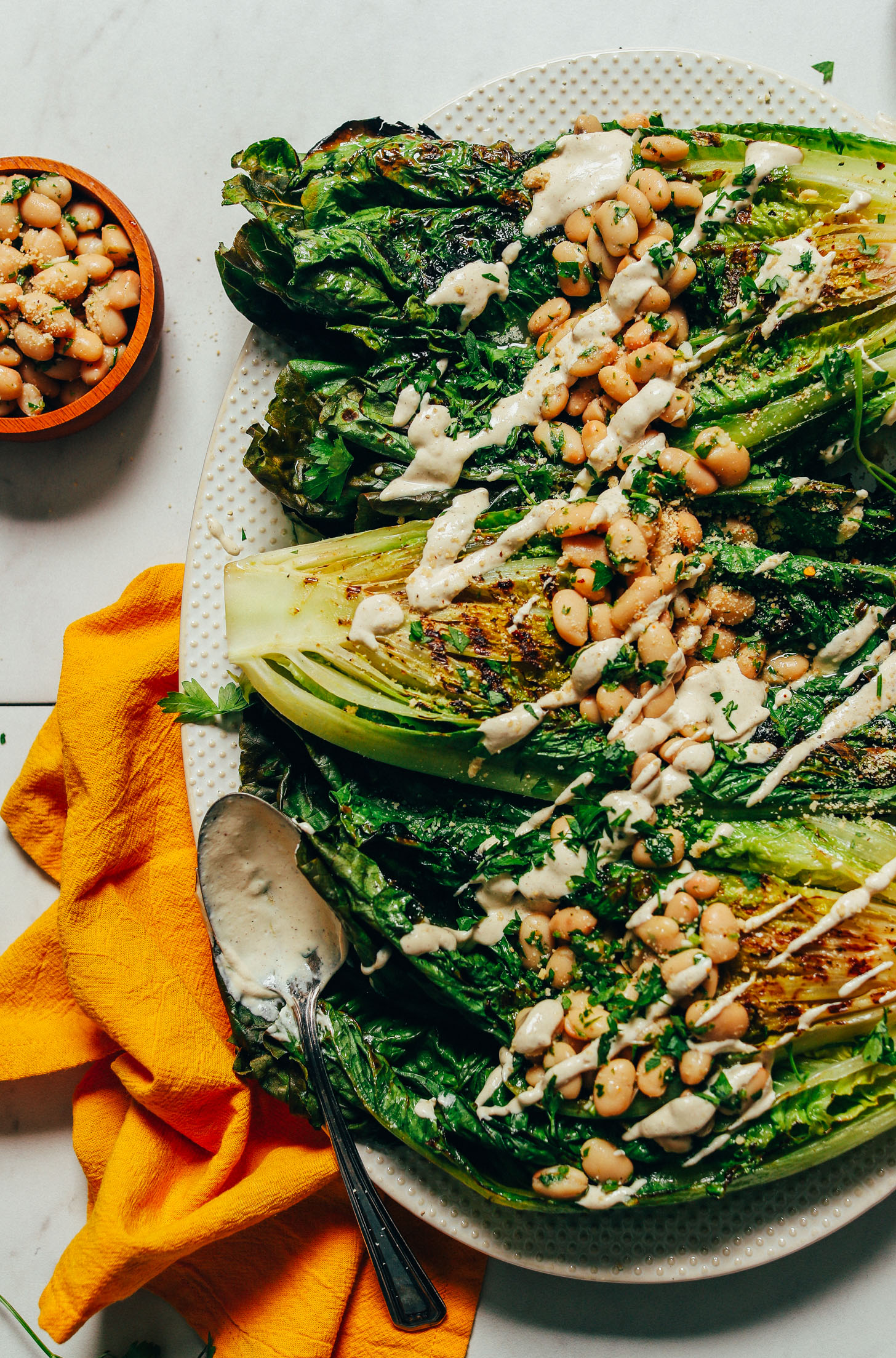 Large platter of Grilled Romaine Salad with Lemon Herbed Beans and a drizzle of Quick Caesar Dressing