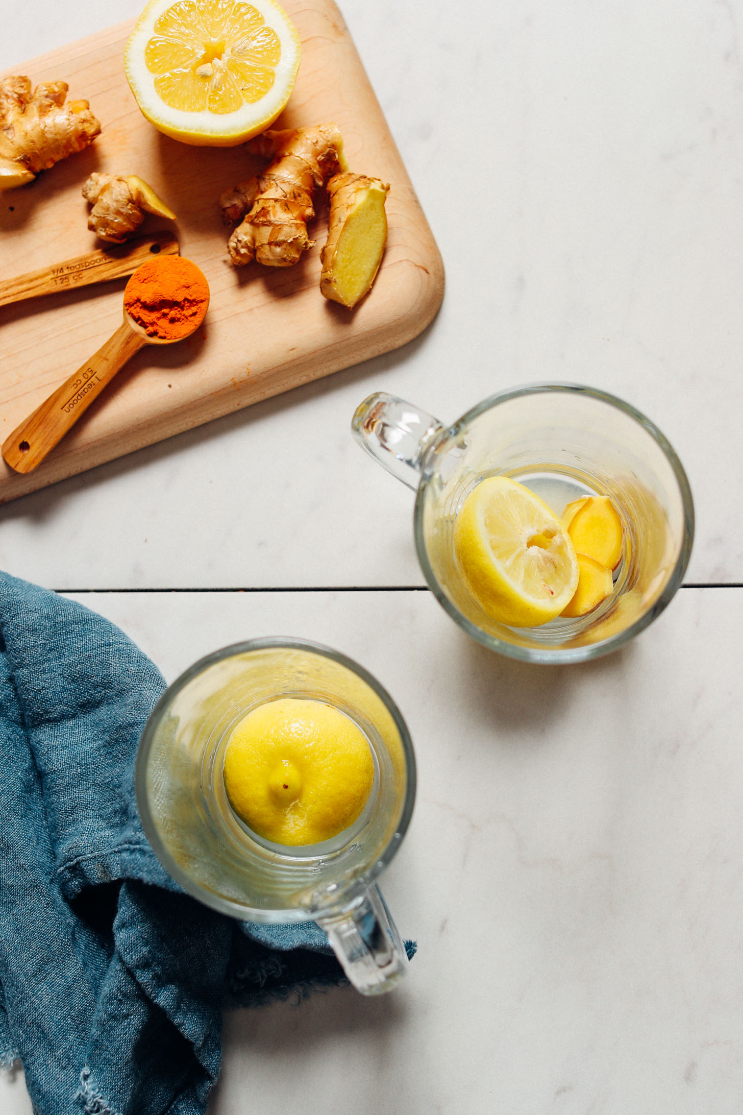 overhead image of two clear mugs with lemon and ginger, a blue towel to the left, and a cutting board above with lemon, ginger, and spices