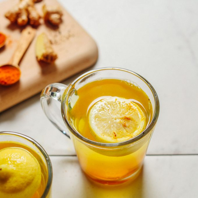 image of lemon ginger water at a 45 degree angle in a clear mug with spoonfuls of spices behind it