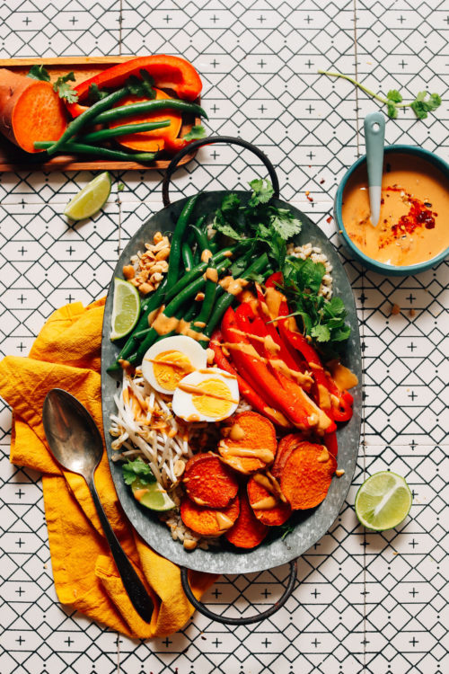 Tray of our delicious Gado Gado recipe beside a bowl of Spicy Peanut Sauce