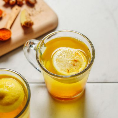 Two glasses of our detoxifying Ginger Lemon Water recipe beside fresh ginger and ground turmeric used to make them