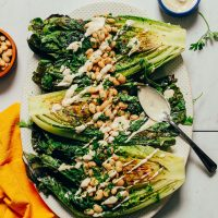 Platter of Grilled Romaine Salad topped with Lemon Herbed Beans and a drizzle of vegan Caesar Dressing