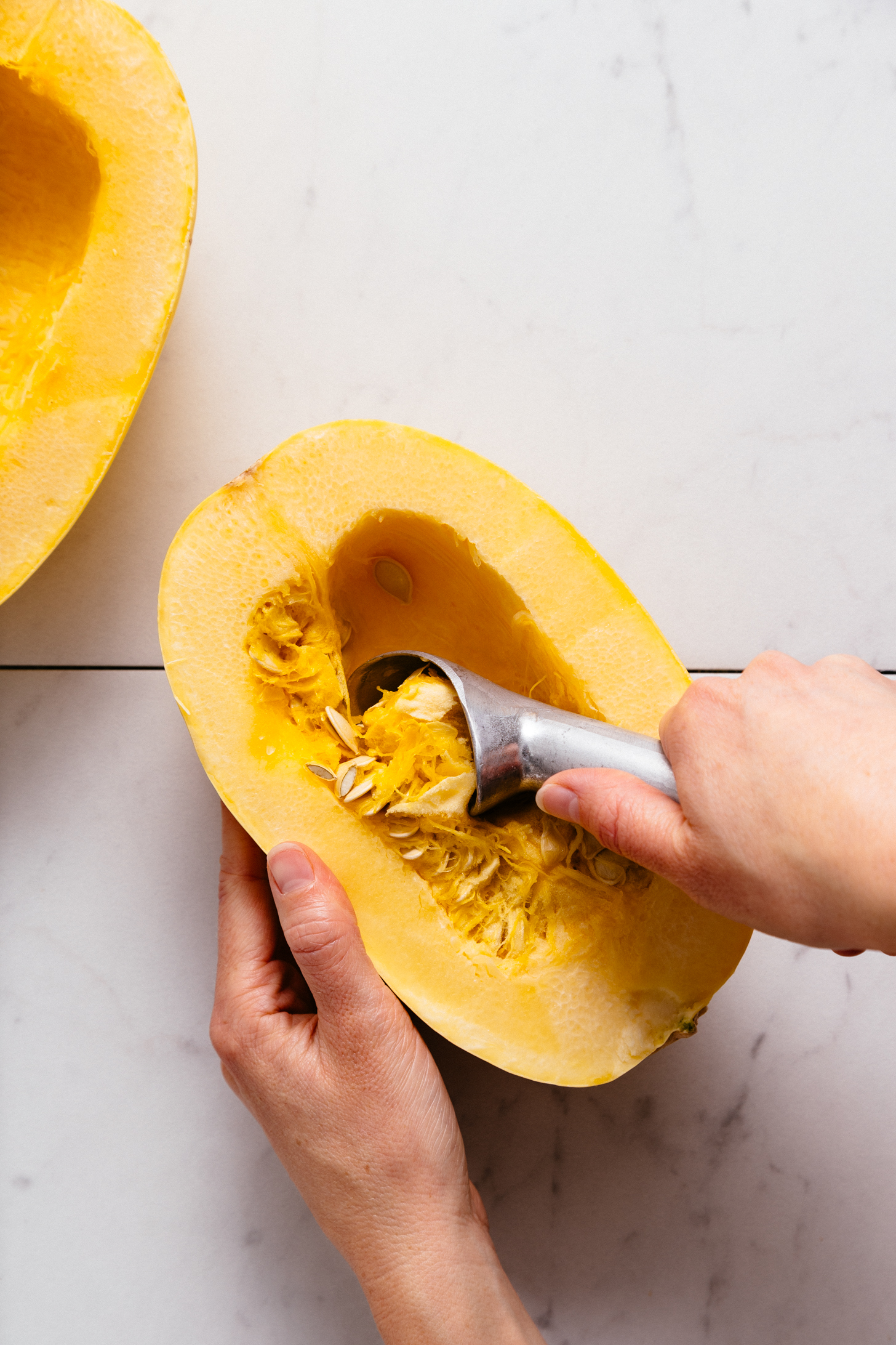 Using an ice cream scoop to remove seeds from a halved spaghetti squash