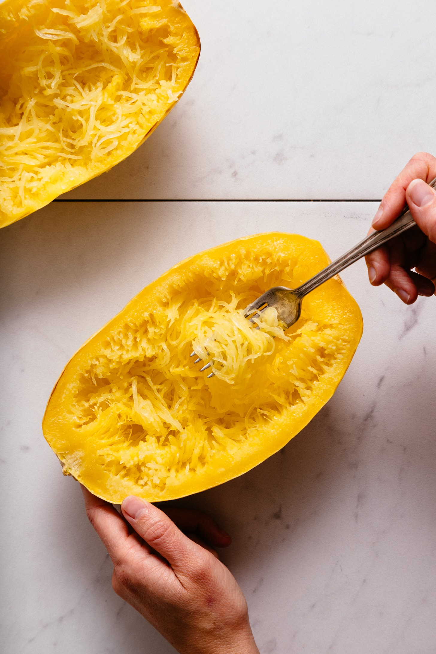 Using a fork to remove strands from a perfectly roasted spaghetti squash
