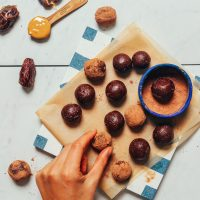 overhead image of date sweetened truffles on a blue and white tile being dipped into cacao powder