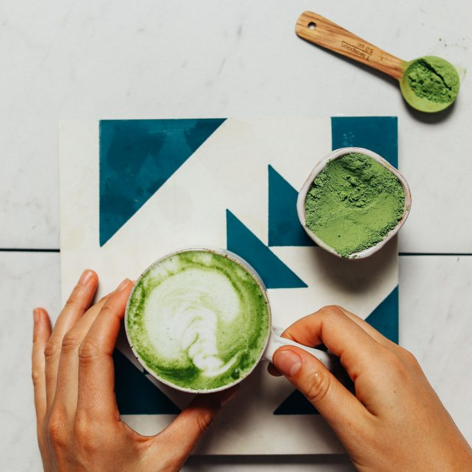 Holding a mug of our No-Matcha Moringa Latte made with cashew oat milk creamer