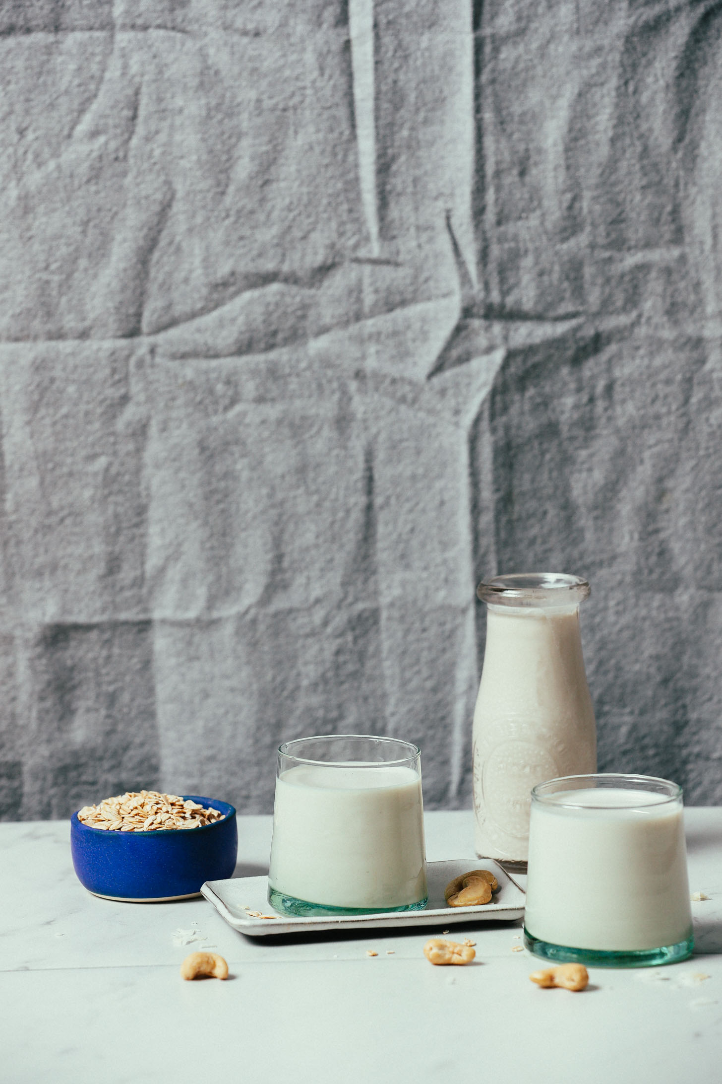 Glasses of homemade Cashew Oat Coconut Milk Creamer surrounded by ingredients use to make it