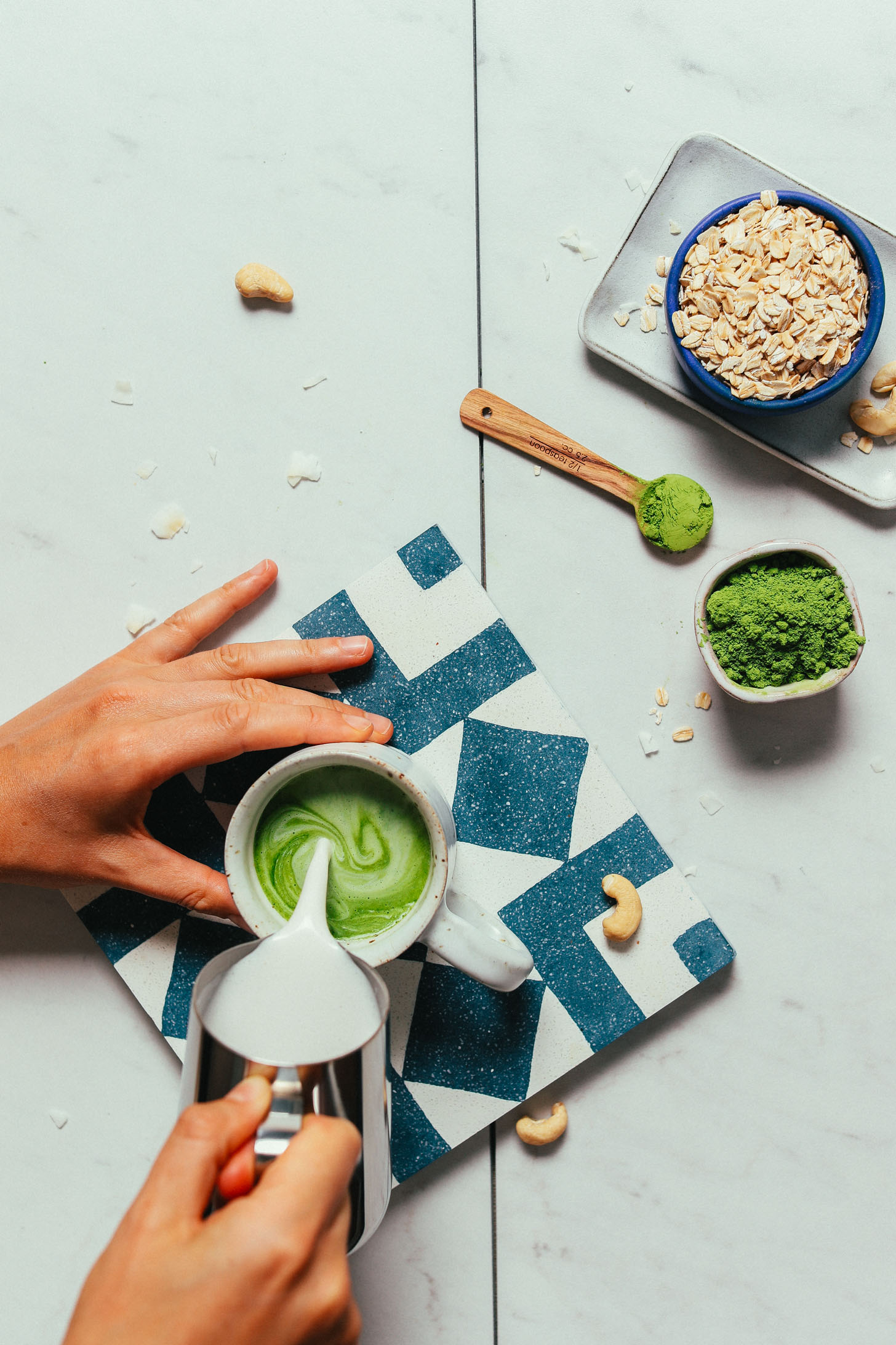 Pouring homemade creamy oat milk into a mug of matcha