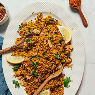 Lemon wedges and fresh cilantro on a platter of our Cauliflower Rice Mujadara recipe