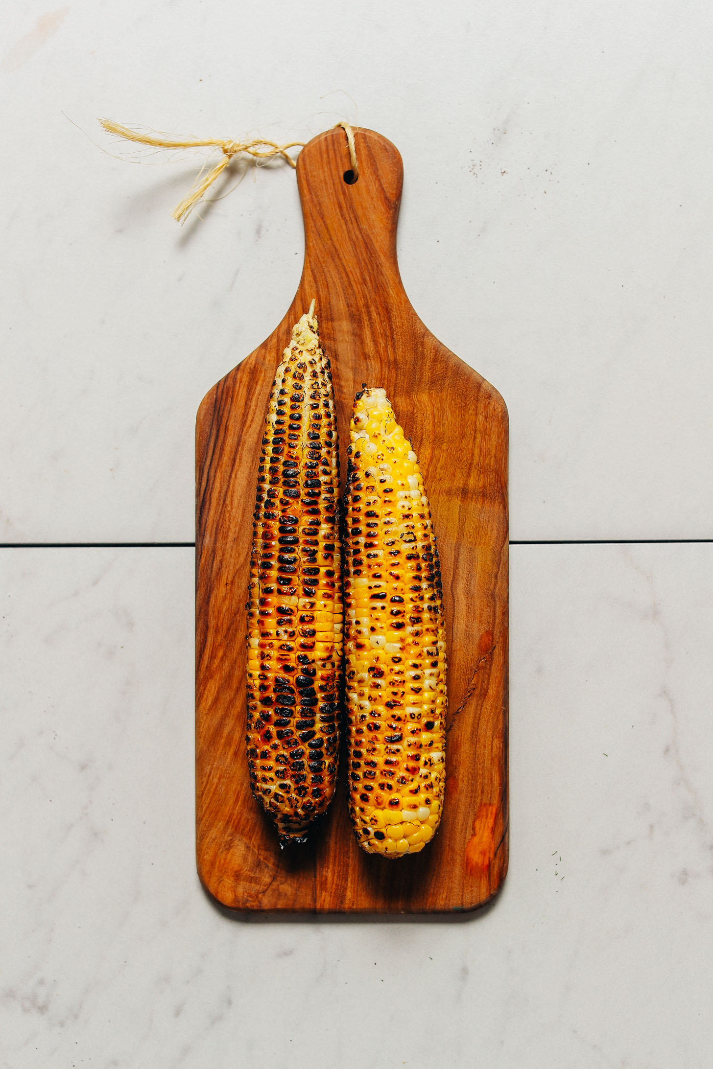 Two ears of grilled corn on a wood cutting board