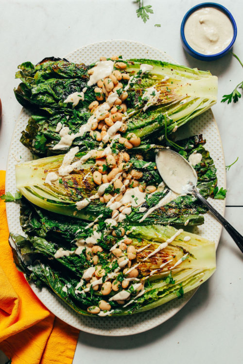 Platter of vegan Grilled Romaine Salad with Lemon Herbed Beans and Quick Caesar Dressing