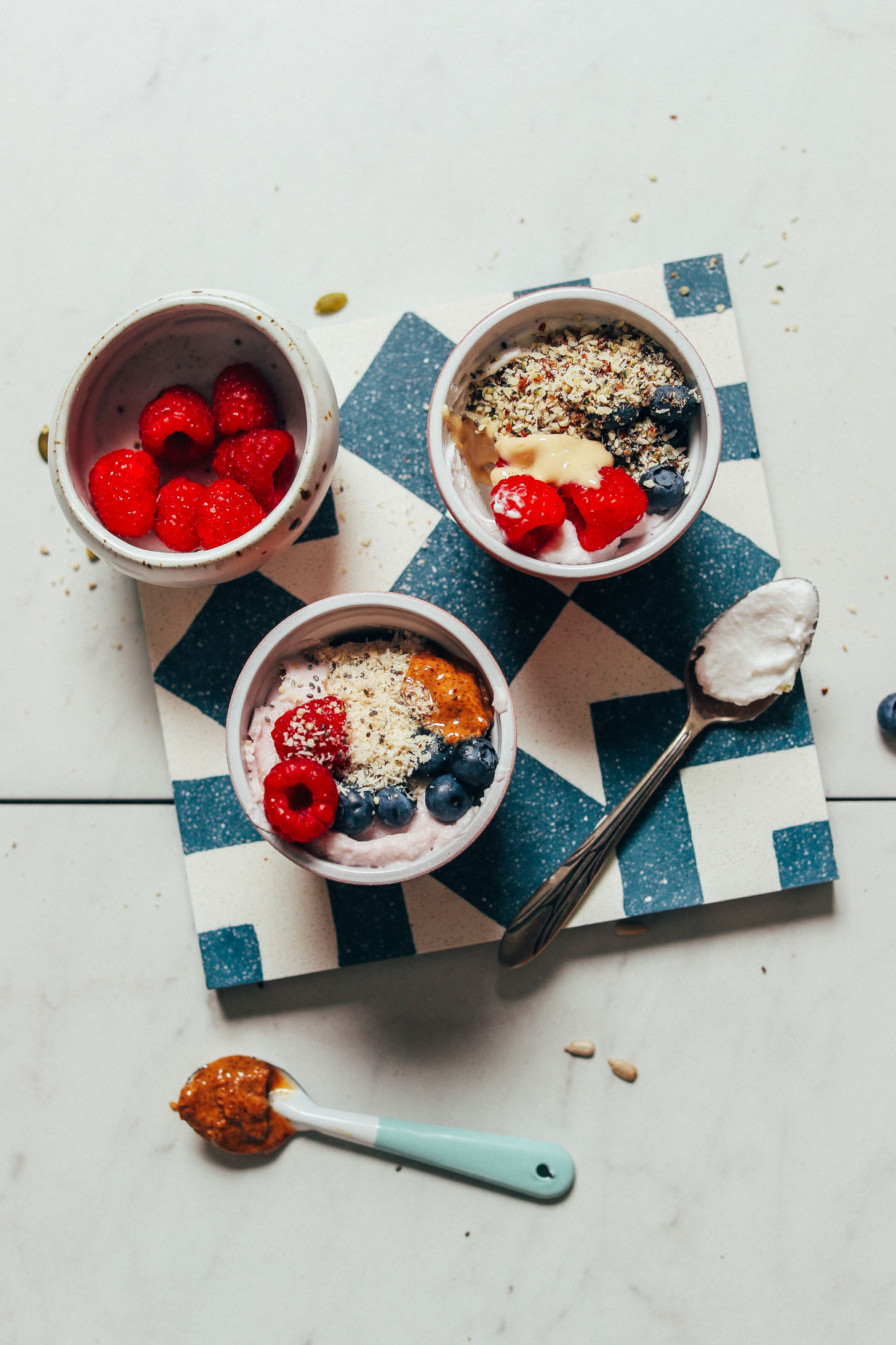 Bowls of dairy-free yogurt with fruit to show a recipe for how to use seed cycling mixes