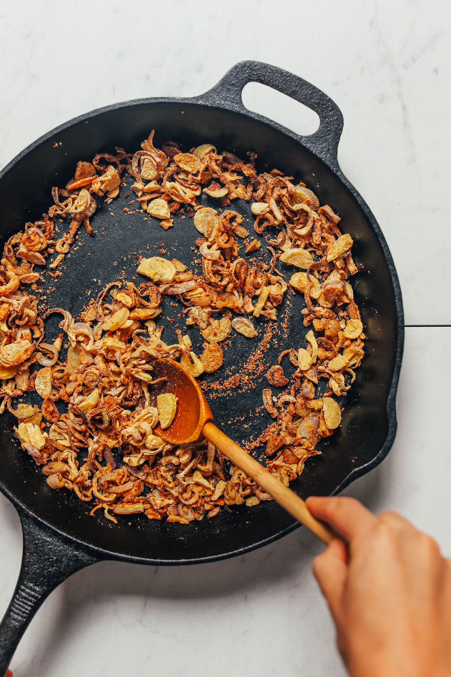 Cooking crispy shallots in a skillet to make our Grain-Free Mujadara recipe