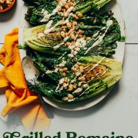 Platter of Grilled Romaine Salad topped with vegan caesar dressing and herbed white beans