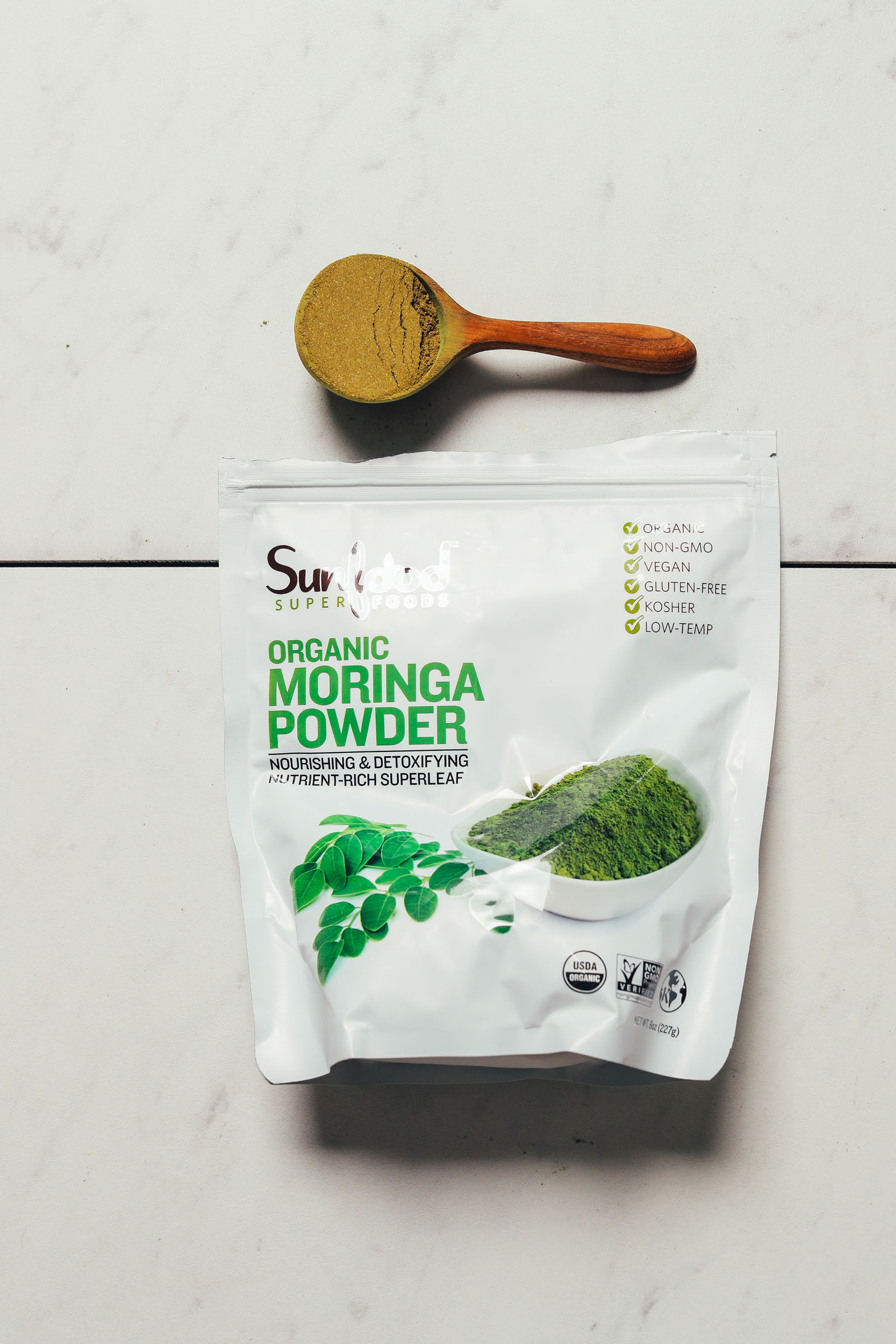 Bag and spoonful of Sunfood Moringa Powder for our review of the top moringa brands
