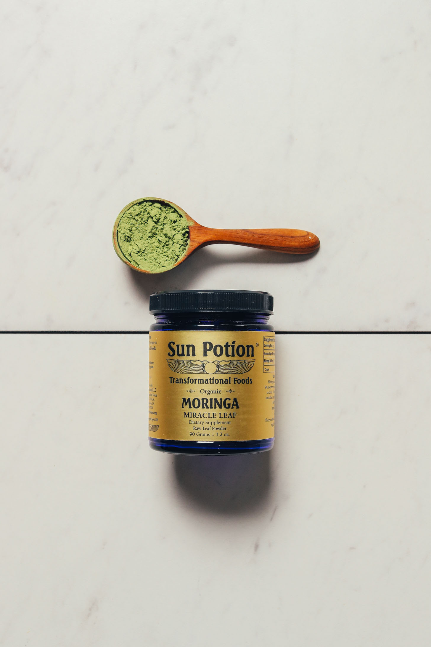 Spoonful and jar of Sun Potion Moringa Powder for our review of the best moringa powder brands