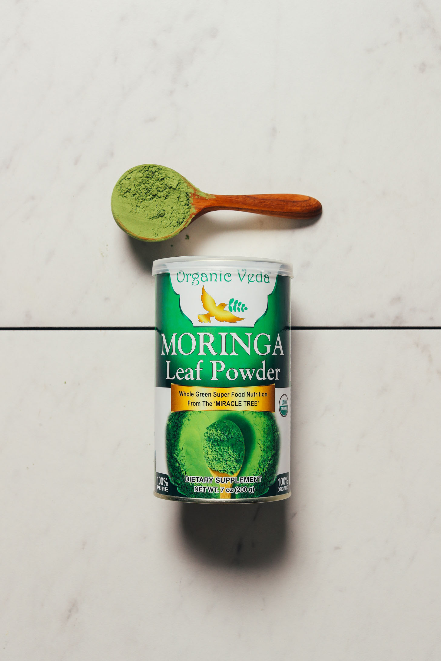 Jar and spoonful of Organic Veda moringa powder for our review of the best brands