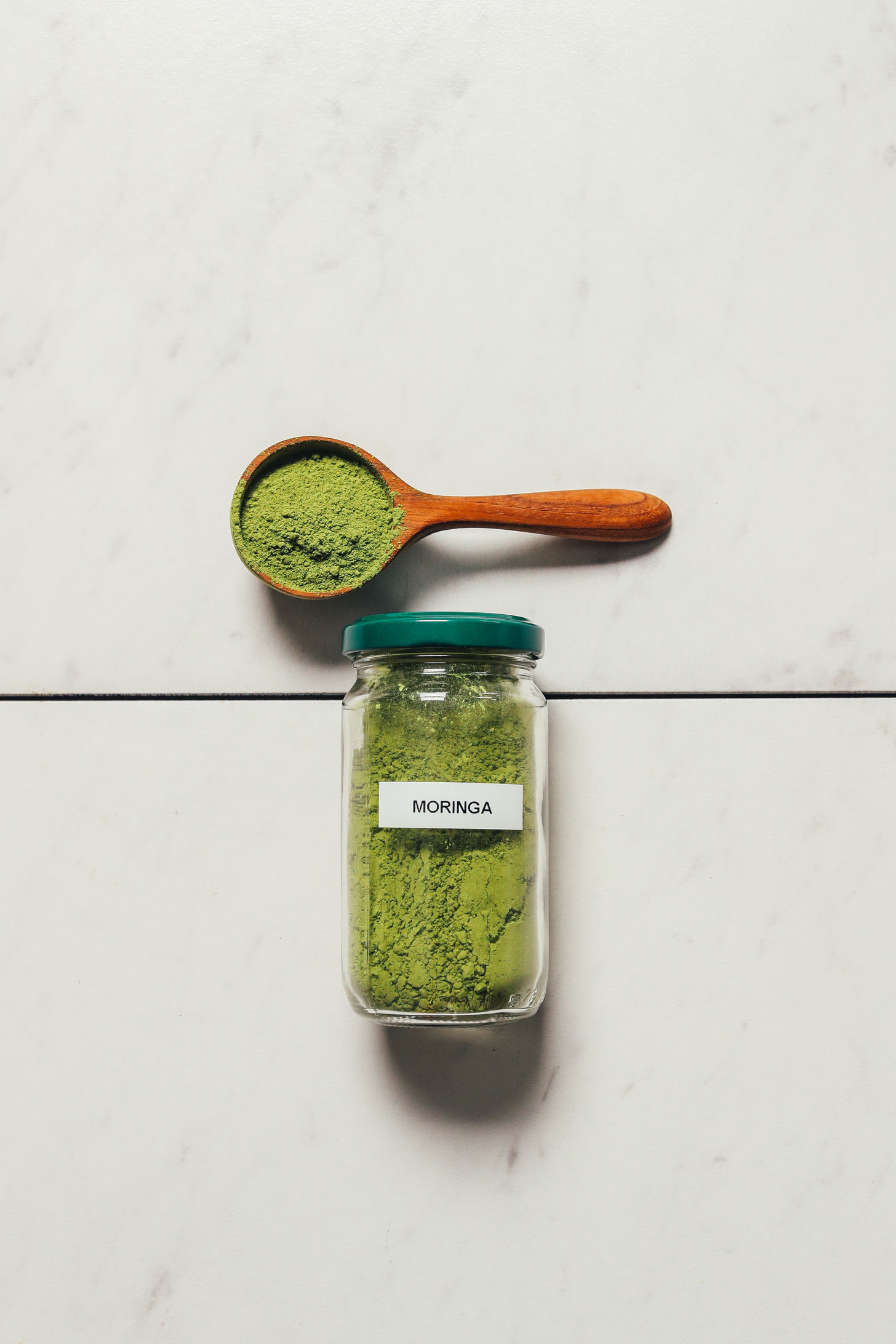 Jar and spoonful of Miracle Garden moringa powder for our top rated moringa powder
