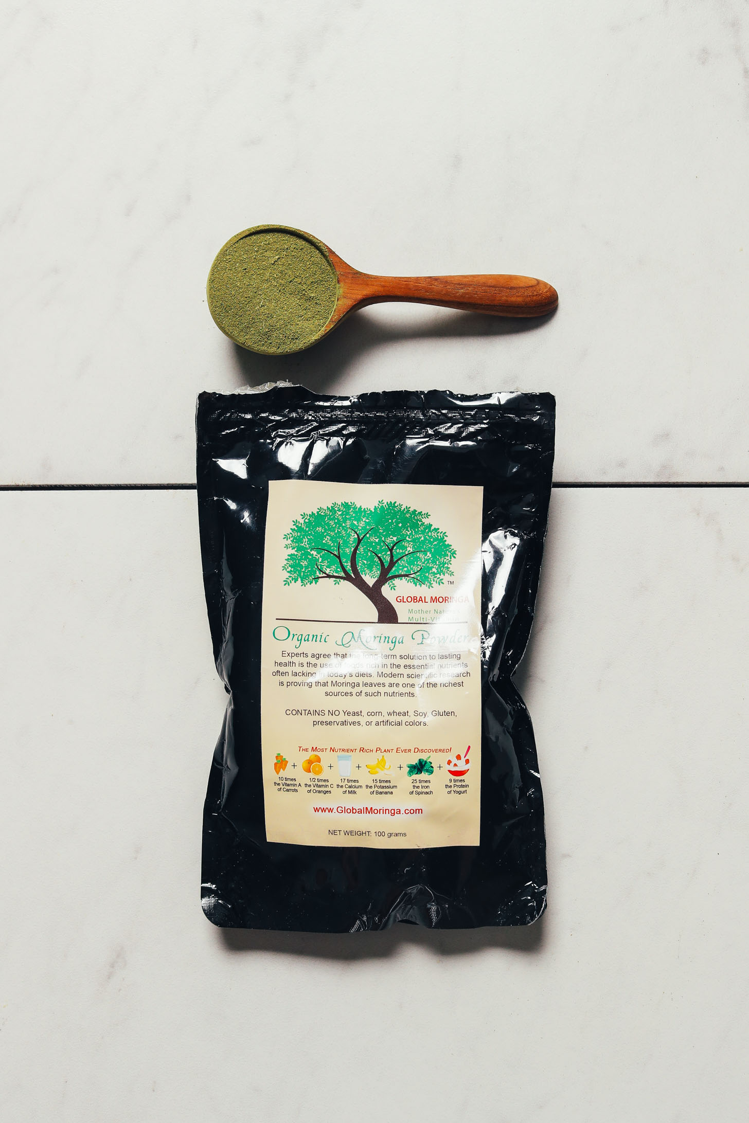 Bag and spoonful of Global Traditions Moringa powder for our review of moringa powder brands