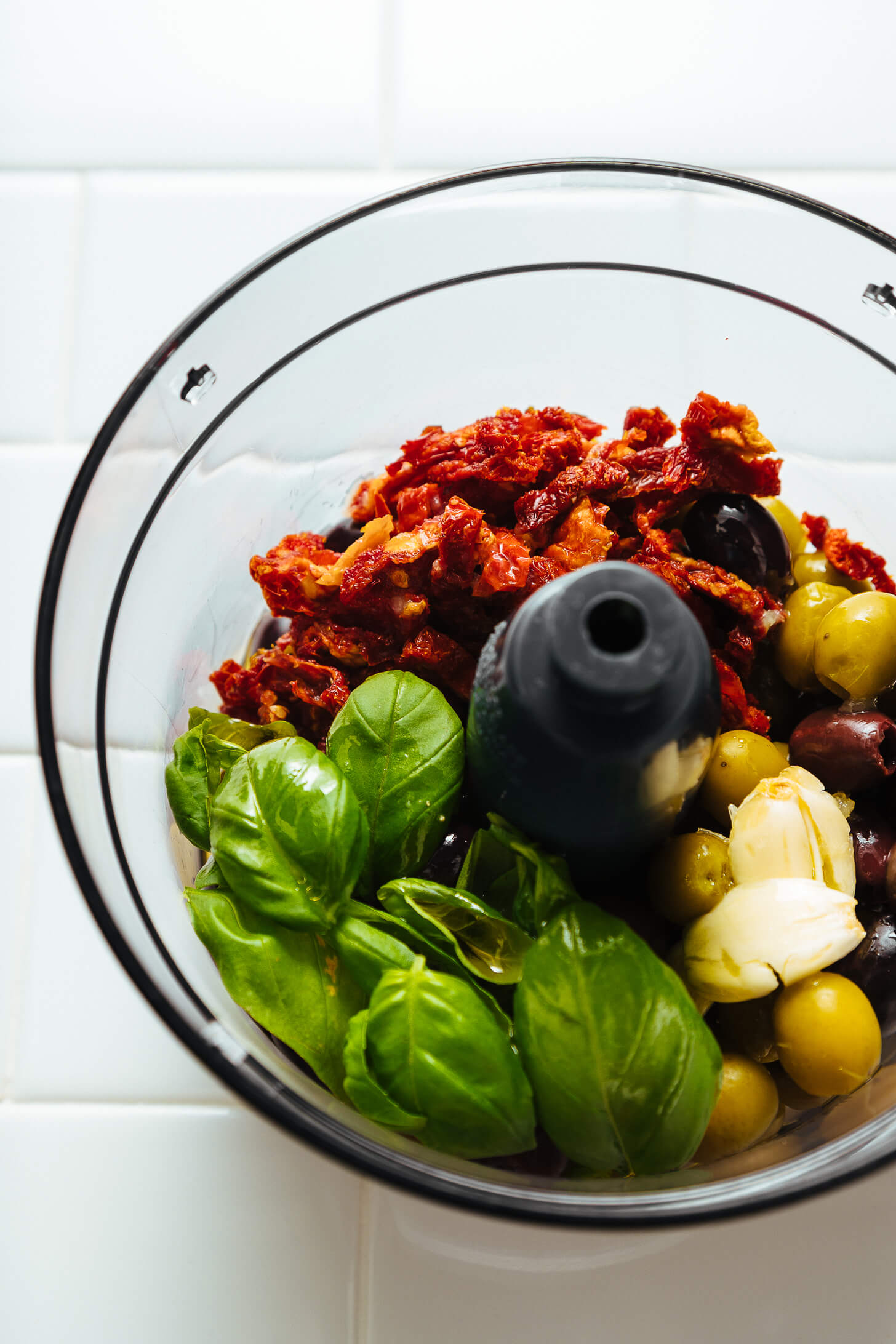 Food processor with ingredients for making our simple Olive Tapenade recipe