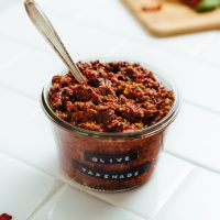 Spoon in a jar of homemade Sun-Dried Tomato and Basil Olive Tapenade
