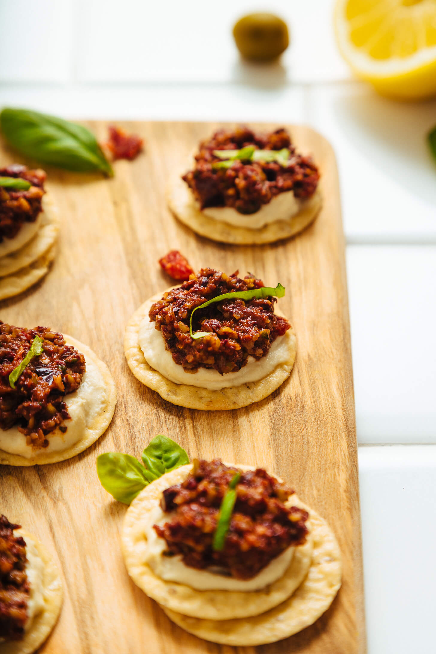 Cutting board of crackers topped with hummus and homemade Sun-Dried Tomato and Basil Olive Tapenade
