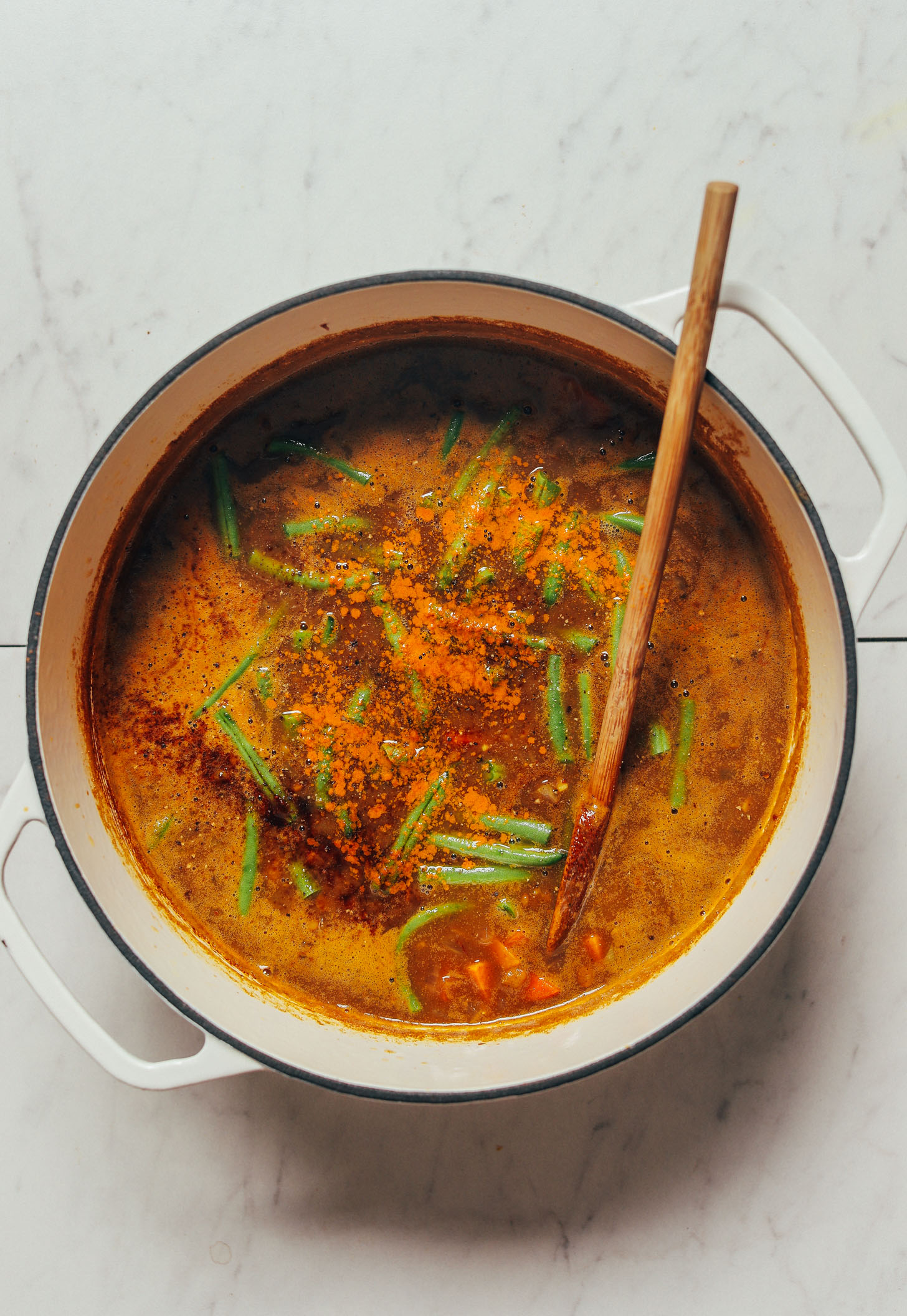 Wooden spoon resting in our 1-Pot Spiced Sweet Potato Lentil Soup recipe