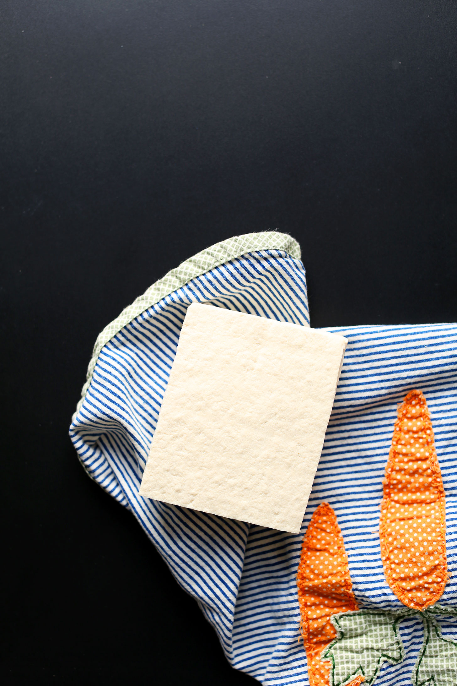 overhead image of a block of tofu being dried on a blue striped towel