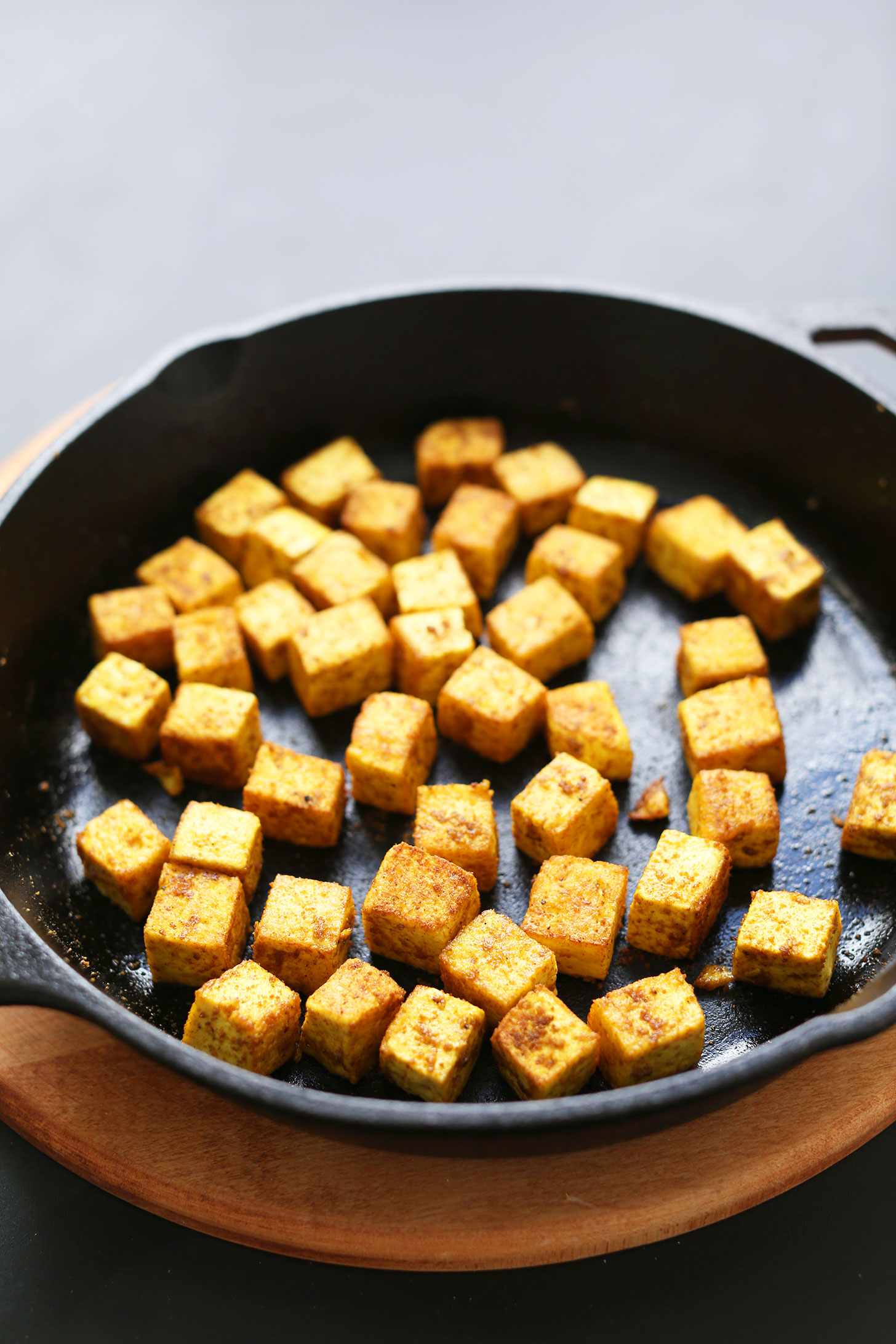 Tofu being sautéed with curry powder in a cast iron skillet