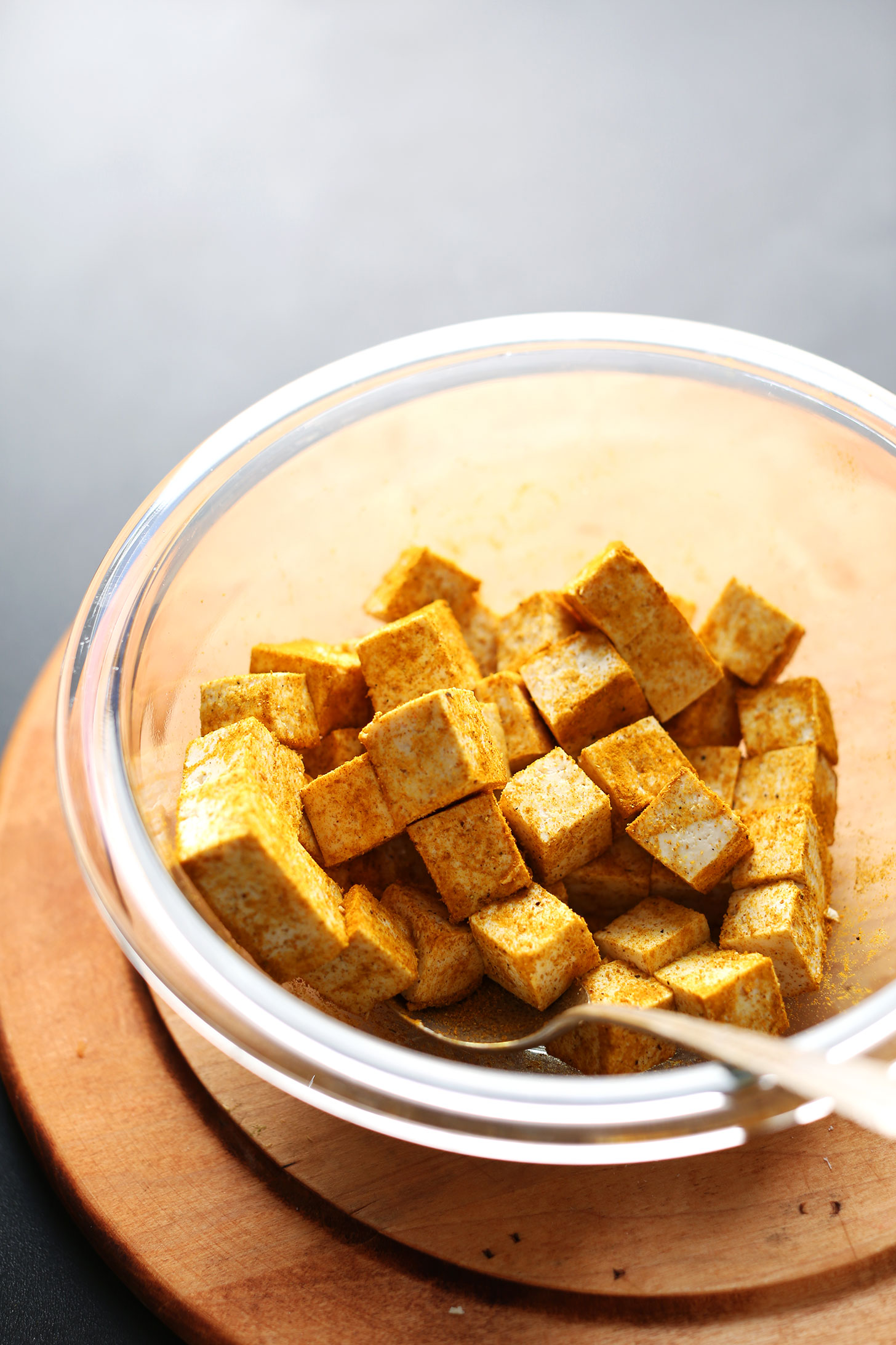 Cubed tofu tossed in curry powder in a glass mixing bowl