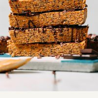 Homemade Peanut Butter Chocolate Protein Bars stacked on a tile