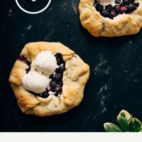 Two mini Blueberry Galettes with scoops of ice cream on a dark background